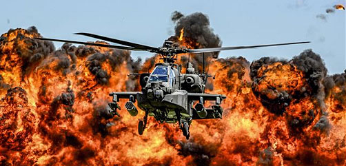 An AH-64D Apache attack helicopter flies in front of a wall of fire during the South Carolina National Guard Air and Ground Expo at McEntire Joint National Guard Base, S.C., May 6, 2017. - ALLOW IMAGES