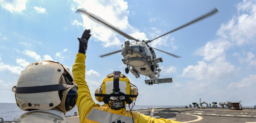 Navy Petty Officer 3rd Class Keith Avinger signals the pilot of an MH-60R Seahawk on the flight deck of the USS Russell in Philippine Sea, March 17, 2020. - ALLOW IMAGES